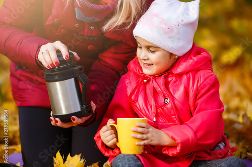 Mother drinking tea with kid daughter 4-5 year old sitting in sun light in park Wallpaper Mural