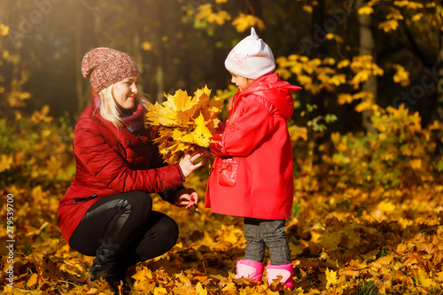 Mother drinking tea with kid daughter 4-5 year old sitting in sun light in park Canvas Print