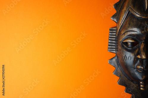 Wooden african mask on orange background - fototapety na wymiar