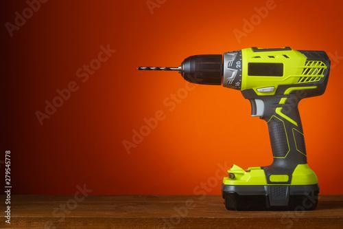 Canvastavla Electric screwdriver on wooden table, orange background