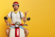 Funny Unshaven Guy In Casual Wear, Drives On Motorcycle, Has Good Trip, Enjoys Freedom, Points Index Finger On Blank Space Over Yellow Wall, Pouts Lips. Professional Driver Bought New Scooter
