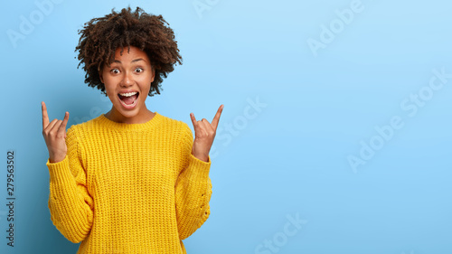 Fotografia, Obraz  Excited lively energized curly woman makes heavy metal gesture, enjoys cool conc