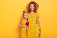 Love You Mum! Pretty Ginger Girl With Red Flower, Embraces Mother, Enjoy Good Time Together. Fashionable Two Sisters In Same Dresses Pose Over Studio Yellow Wall. Motherhood, Parenthood Concept