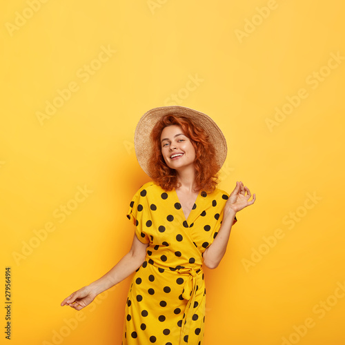 Valokuva  Pretty carefree lady dances and looks with eyes full of happiness, tender smile,