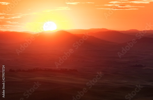 Marron Sun rising over the rolling hills and farm land in palouse, washington