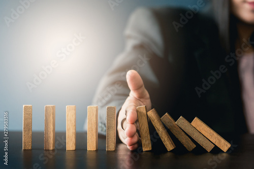 Aluminium Prints Equestrian Close up of businessgirl hand Stopping Falling wooden Dominoes effect from continuous toppled or risk, strategy and successful intervention concept for business.