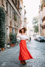 Portrait Of A Girl In A Red Dress And Hat. Stylish Bride On The Streets Of Rome.