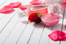 Perfume, Body Care And Beauty Products With Red Roses, Pink Petals On White Wood Table