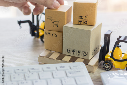 Mini forklift truck load cardboard boxes with symbols on wood pallet and fingers over its and keyboard nearby Canvas Print