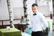 A Young, Handsome Waiter Is Holding A Tray In A Carafe Of Water. The Concept Of The Restaurant Business. The Staff In The Field Of Restaurant Business.