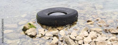 ein alter Reifen liegt am Ufer Tapéta, Fotótapéta