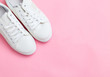 canvas print picture - Toes of white trendy sneakers on pink background. Place for text.