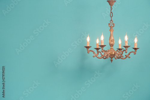 Fotografía Retro antique old bronze chandelier with bulb lamps shaped candles hanging front mint blue wall background