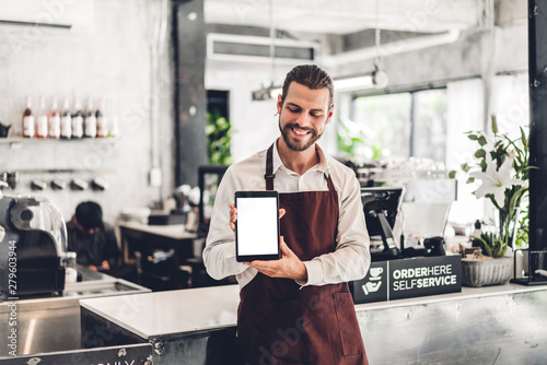 Portrait of barista man small business owner standing with tablet computer with mockup blank in the cafe or coffee shop in a cafe - 279603944