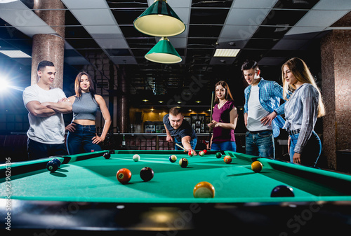 Papel de parede Group of young cheerful friends playing billiards.
