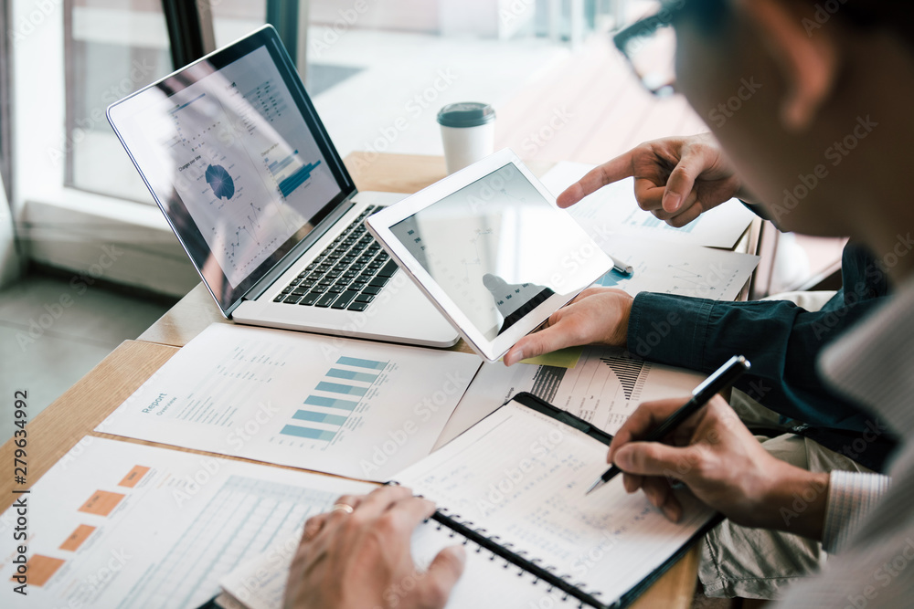 Fototapeta Business partnership coworkers using a tablet to analysis graph company financial budget report and cost work progress and planning for future in office room.