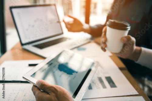 Business partnership pointing to the graph company financial statements report and profits earned during in the computer screen with giving a presentation to colleagues holding tablet. - 279635118