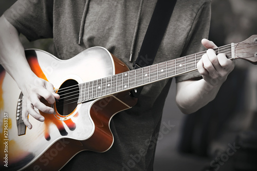 Papiers peints Musique A professional musician plays an improvised melody on a six-string acoustic beautiful guitar, holding a mediator in his hand. Photo in black and white to highlight the brightness of the music