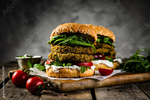 Obraz Vegan zucchini burger and ingredients on rustic wood background, copy space - fototapety do salonu