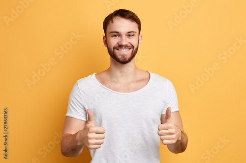 Happy cheerful man giving thumbs up Wallpaper Mural
