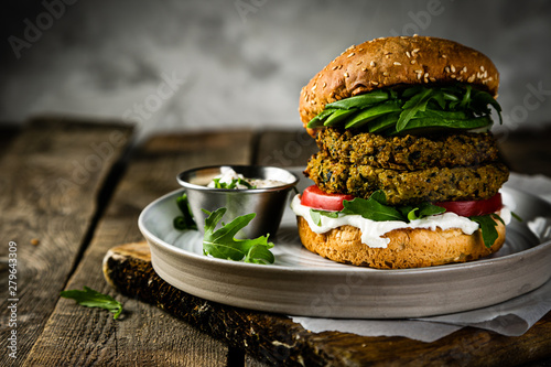 Vegan zucchini burger and ingredients on rustic wood background, copy space