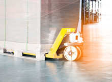 Hand Pallet Truck With Cargo Pallet At Warehouse.