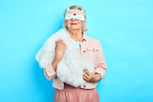 Beautiful Smiling Old Lady In Sleeping Mask Posing To The Camera. Close Up Photo. Isolated Blue Backgrouns . Studio Shot