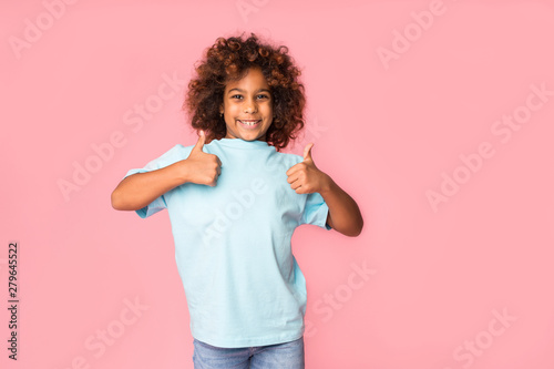 Fotografiet  African-american girl showing thumbs up on background