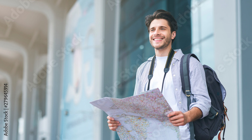 Tourist man looking for route on map at airport - fototapety na wymiar