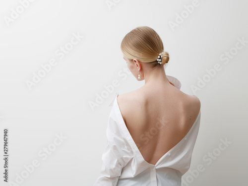 Minimalist photo, Fashionable girl in stylish summer things - white shirt. View from the back. Earrings, a ring . Street fashion , blogger style . Beauty . Minimalist Fashion clothes