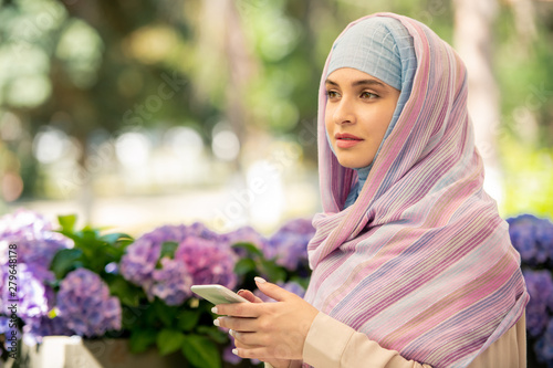 Fotografía  Pretty young muslim woman in hijab scrolling in smartphone outdoors