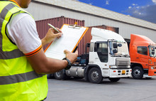 Worker Man Hodling Clipboard Is Checking And Loading Control A Truck Docking At Distribution Warehouse.