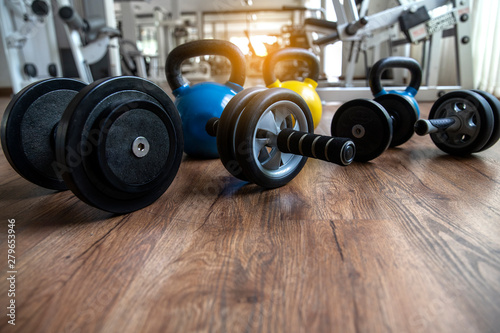 Fotografia  Hand weights Fitness exercise equipment dumbbell, Ab roller and kettlebells weights on wood floor in gym background