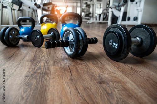 Hand weights Fitness exercise equipment dumbbell, Ab roller and kettlebells weights on wood floor in gym background Obraz na płótnie