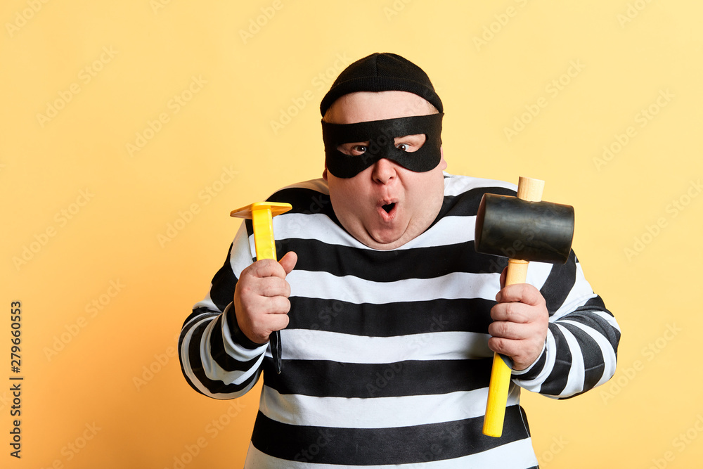 Fototapeta excited funny man in mask being excited by stolen money. studio shot