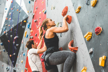 nekoliko sportaša koji se penjaju na strmoj stijeni, penjući se na umjetni zid u zatvorenom. Koncept ekstremnih sportova i balvaniranja