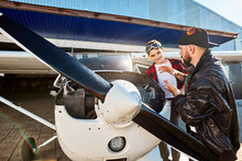 Young Male Pilot Tells Funny Story, Stands Near White Light Propeller Airplane, Sweet Little Boy Listens And Looks At Him With Joyful Smile. Hangar Bulding On The Background, Outdoor Shot.