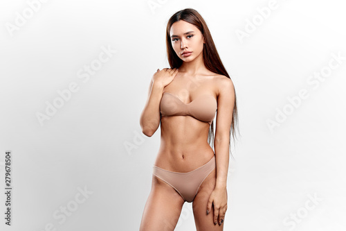 Obraz sensual young model with a palm on her shoulder looking at the camera. sexuality, fashion, people concept. isolated white background. studio shot - fototapety do salonu