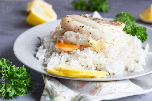 Recess Fitting Appetizer Fish baked with carrot, onion, parsley and sliced lemon on a grey plate with rice. Healthy dinner.