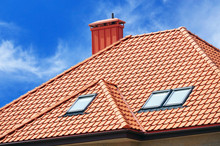 Roof Of The House Of Red Tiles On Background Sky