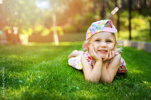 little girl laying on green grass with hands on cheeks at home backyard on sunny Tapéta, Fotótapéta