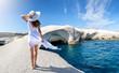 canvas print picture - Attraktive Frau in weißem Sommerkleid genießt die einzigartige Landschaft von Sarakiniko auf der insel Milos, Kykladen, Griechenland
