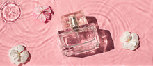 Glass Cosmetic Bottle In The Water On The Pink Background Flat Lay. Top View