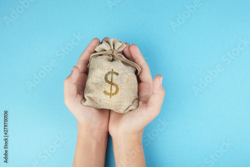 Fototapeta Women hold a money bag on blue background, Saving money for future investment concept. obraz