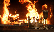 Golden Crown And A Goblet Full Of Gold On The King Table Over Burning Fire Background.
