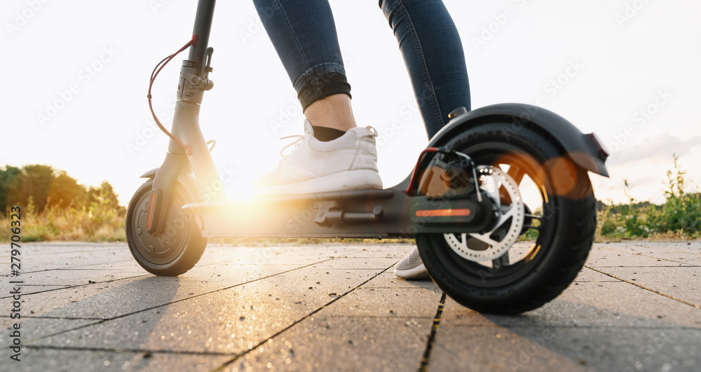 Fototapety, obrazy: Young woman is ready to discover the urban city at sunset with electric scooter or e-scooter, Electric urban transportation concept image
