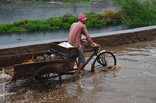 Fotografía インドの首都のデリー 洪水した道路を自転車で走るインド人男性