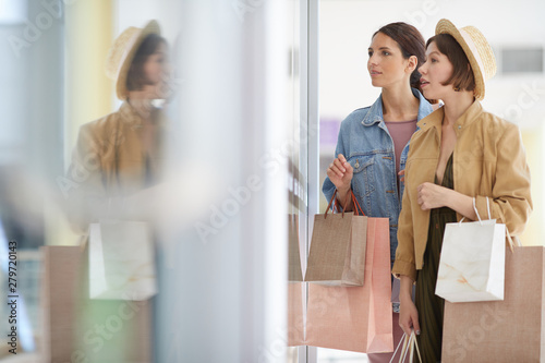 Obraz na plátně Young excited women in jackets standing at storefront and choosing clothing toge
