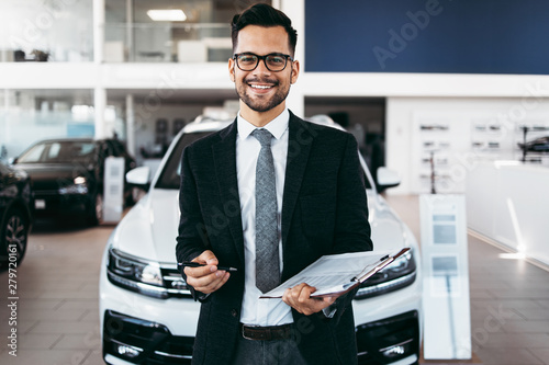Good looking, cheerful and friendly salesman poses in a car salon or showroom Canvas-taulu