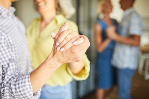 Fototapeta Closeup of unrecognizable senior couple dancing romantically holding hands, copy